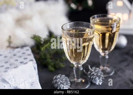 Two glasses with champagne at gray background, mandarins, cones, presents, tinsel and christmas toys near. Christmas composition - Stock Photo