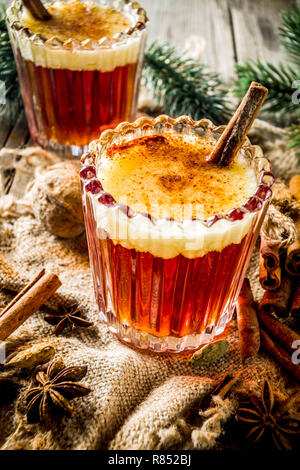 Winter holidays traditional drink, homemade hot buttered rum with spices, over old rustic wooden background with christmas tree branches, copy space - Stock Photo