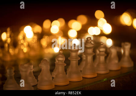 close up of a glass chess set with warm lights in the background - Stock Photo