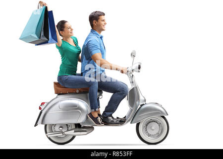 Full length profile shot of a young couple riding on a vintage motorbike with shopping bags isolated on white background - Stock Photo
