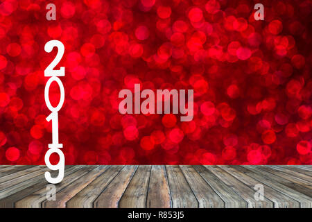Happy new year celebration wooden cut number 2019 on top of perspective wood table montage with red bokeh as background and space for decoration. Back - Stock Photo