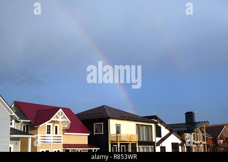 Landscape with rainbow after rain above modern cottage village homes in summer day horizontal photo - Stock Photo