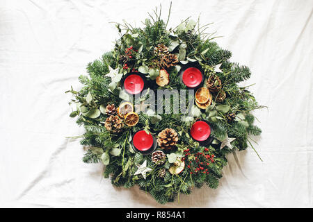 Christmas advent wreath isolated on white table background. Decorated by evergreen fir tree branches, eucalyptus leaves, wooden stars, pine cones, berries and red candles. Flat lay, top view. - Stock Photo