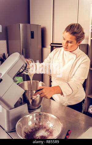 It is done. Positive nice woman looking at the kitchen machine while taking the bowl with dough - Stock Photo