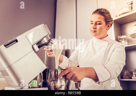 Favourite job. Nice serious cook focusing on the preparation process while mixing different ingredients - Stock Photo
