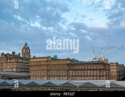 Edinburgh grand buildings in Winter dawn. Rocco Forte Balmoral Hotel with clock tower and Waverley station glass roof, Scotland, UK - Stock Photo