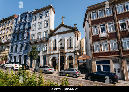 Porto, Portugal - December 27, 2018 : View of a street with Chapel of Our Lord Saviour of the World porto between houses. - Stock Photo