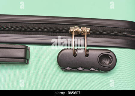 Closeup of a security padlock with three numbers on green suitcase - Stock Photo