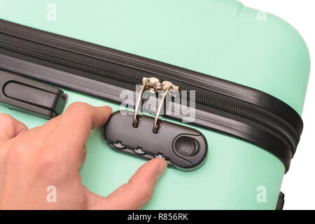 Hand opens suitcase combination lock on the green suitcase. - Stock Photo