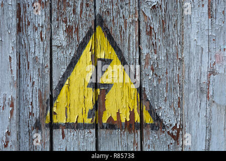 Old rusty sign danger high voltage on a wooden wall with peeling off white paint. - Stock Photo