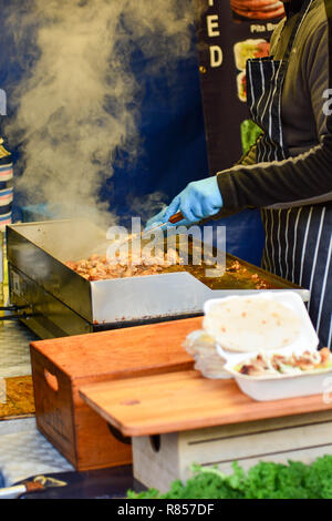 Street food vendor cooking pieces of chicken on portable hotplate at local food market - Stock Photo