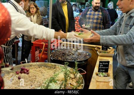 An Italian chef handing a customer a food carton with hot wild mushroom spelt risotto cooking at a Borough Market stall London England UK KATHY DEWITT - Stock Photo