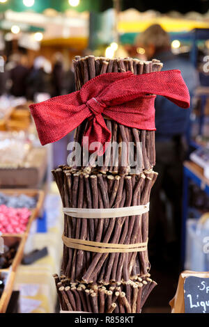 Liquorice raw sticks (licorice) Glycyrrhiza glabra with a red Christmas bow on a stall at Borough Market Christmas in London England UK   KATHY DEWITT - Stock Photo