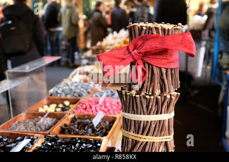 Borough Market Christmas raw liquorice sticks (licorice) Glycyrrhiza glabra with a red Christmas bow on sweets stall London England UK   KATHY DEWITT - Stock Photo