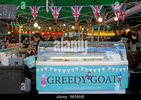 Borough Market food stall sign Greedy Goat goats milk ice cream refrigeration unit and worker with Union Jack bunting London England UK  KATHY DEWIT - Stock Photo