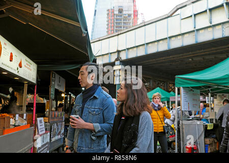 A young couple checking out a food stall at Borough Market in London England UK  KATHY DEWITT - Stock Photo