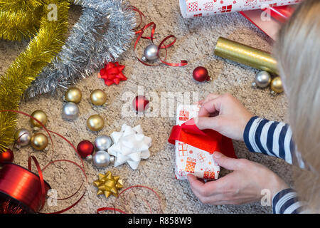 Woman prepare Christmas present with paper and red ribbon - Stock Photo