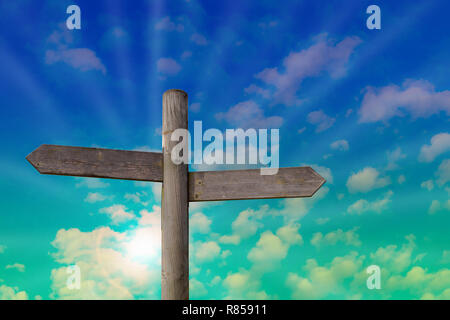 A wooden signpost with two empty arrows for your own text. Background with a light cloudy sky and light sun beams. - Stock Photo