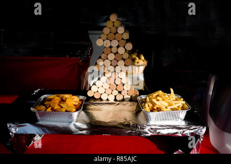 fast food stand at a christmas fair in france, displays 2 tinfoil containers with different types of handcut chips next to xmas tree built from corks - Stock Photo