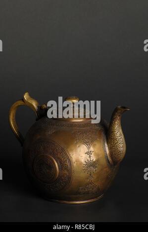 ancient oriental metal teapot on dark background. antique bronze tableware - Stock Photo
