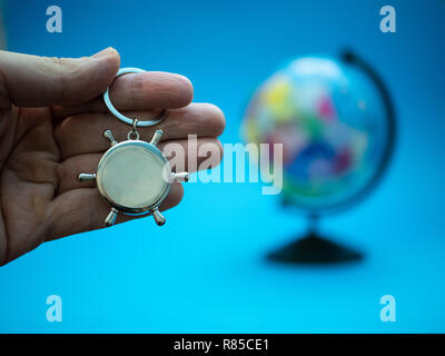 hand with naval ship steering wheel and globe blurred on background, selective focus on foreground. overseas global delivery business concept - Stock Photo