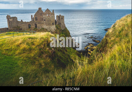 Dunluce castle on the green covered cliff. Irish shoreline. Overwhelming Northern Ireland landscape. Ancient now-ruined Medieval building with the ocean view. Famous archeological and touristic site. - Stock Photo