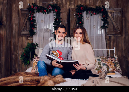 Spending nice time at home. Beautiful young loving couple bonding to each other and smiling while woman holding a book. - Stock Photo