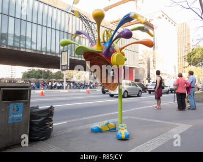 "Passersby stand behind funny 'Vivo connected' phone booth street art installation, as part of ""Call Parade"", Avenida Paulista, Sao Paulo, Brazil - Stock Photo"