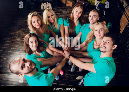 Portrait of happy fit young female friends stacking hands. - Stock Photo