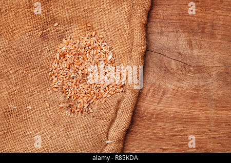 wheat seeds in a canvas sack on a wooden desc - Stock Photo