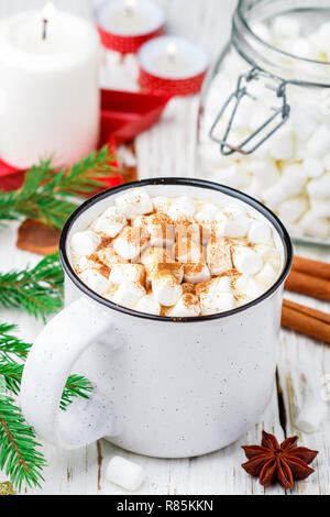 Hot cocoa (coffee or chocolate) with marshmallows and cinnamon in a white Cup. Candy, candles and fir branches on the table. Christmas. New year. Rust - Stock Photo