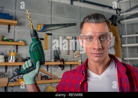 Handsome smiling caucasian young man in plaid shirt, safety eye glasses on for protection, gloves drilling with power drill, working in carpentry workshop - Stock Photo