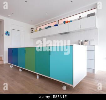 Custom designed kitchen island in open plan kitchen, on industrial castor wheels, retro design painted in blue and green ombre colours. - Stock Photo
