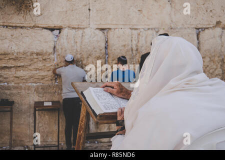 Religious orthodox jew praying at the Western wall and reads the Torah in Jerusalem old city. - Stock Photo