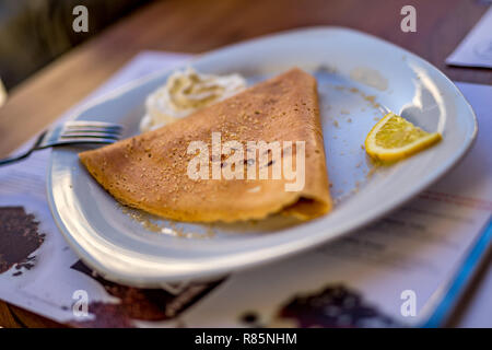 Selective shallow focus of one delicious crepe, European pancake, in white plate served Greek style with brown sugar and slice of lemon and creme in s - Stock Photo