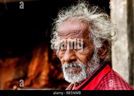 Vadodara, 30 september 2018: close up portrait headshot of old indian ermit sadhu with sad red eyes and grey hair walking outodoors - Stock Photo