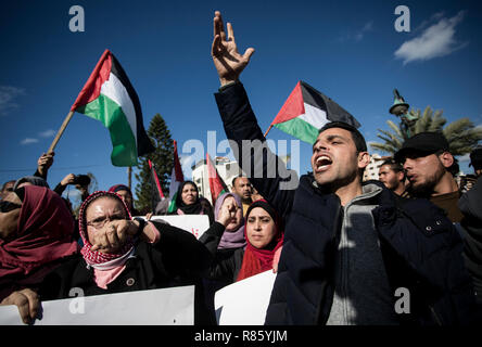 Gaza, Palestinian territory. 13th December, 2018. Protesters are seen holding placards and flags while chanting slogans during the protest. Supporters of the Palestinian factions participated in a protest, following the killing of the three Palestinians by the Israeli army in the West Bank. Credit: SOPA Images Limited/Alamy Live News - Stock Photo