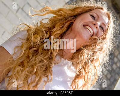Hamburg, Germany. 09th Sep, 2018. 09.09.2018, Hamburg: Lisa (27) laughs at the end of the meeting of redheaded people from all over Germany. Natural red hair is rare, at most two percent of the world's population are real Redheads. The meeting of redheaded people from all over Germany is organized by the editor of the 'Magazine for redheads'. Credit: Axel Heimken/dpa | usage worldwide/dpa/Alamy Live News - Stock Photo