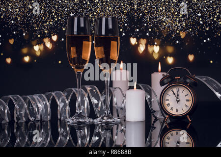 Two wine glasses with champagne,lights, clock and candles on a black background with reflection. Copy space. Merry Christmas and Happy New Year, backg - Stock Photo