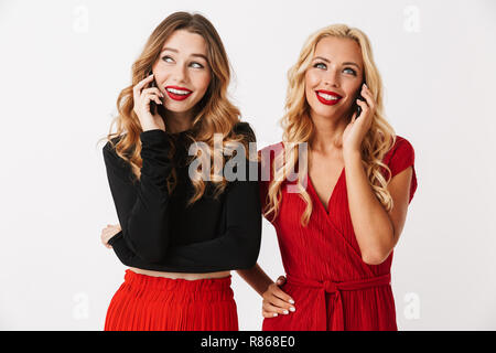 Portrait of two pretty young smartly dressed women wearing makeup standing isolated over white background,talking on mobile phones - Stock Photo