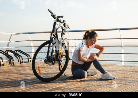 Beautiful young fitness girl outdoors with a bicycle, sitting, suffering from a knee pain - Stock Photo