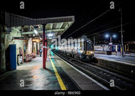 Glasgow Express passenger train passing through Oxenholme Railway Station - Stock Photo