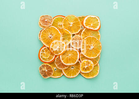 Dried citrus slices lemons & oranges on turquoise colored background. Homemade Christmas natural decoration. Square shape, Flat Lay. - Stock Photo