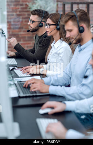 close up.call center operators sitting at the Desk. - Stock Photo