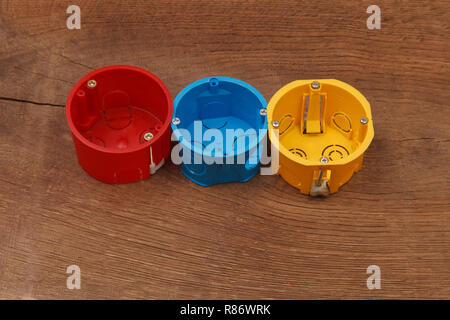 Plastic enclosure for installation of electrical household appliances on wooden background - Stock Photo