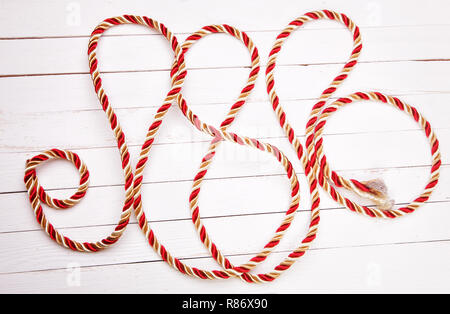 Red rope on a white background wooden table - Stock Photo