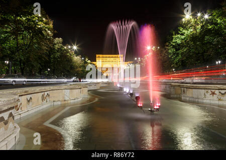 Building of Romanian parliament in Bucharest in a beautiful summer night, and fountains in front. - Stock Photo