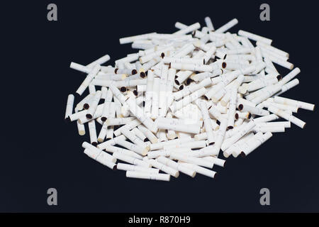 Newest electronic cigarettes, heating tobacco system IQOS, smoking, dark blue isolated on black background. mountain of used cigarettes, sticks - Stock Photo