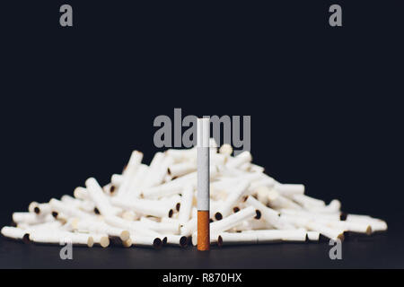 Newest electronic cigarettes, heating tobacco system IQOS, smoking, dark blue isolated on black background. mountain of used cigarettes, sticks classic cigarette on the background of new sticks - Stock Photo