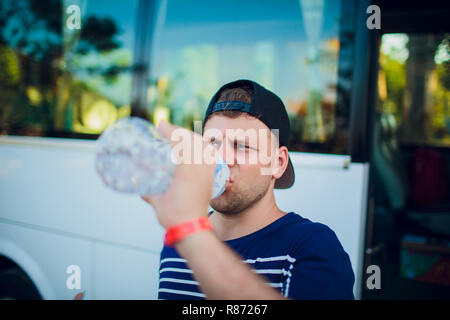 Handsome man drinking water after running outdoors on the background of the bus, tourist. - Stock Photo